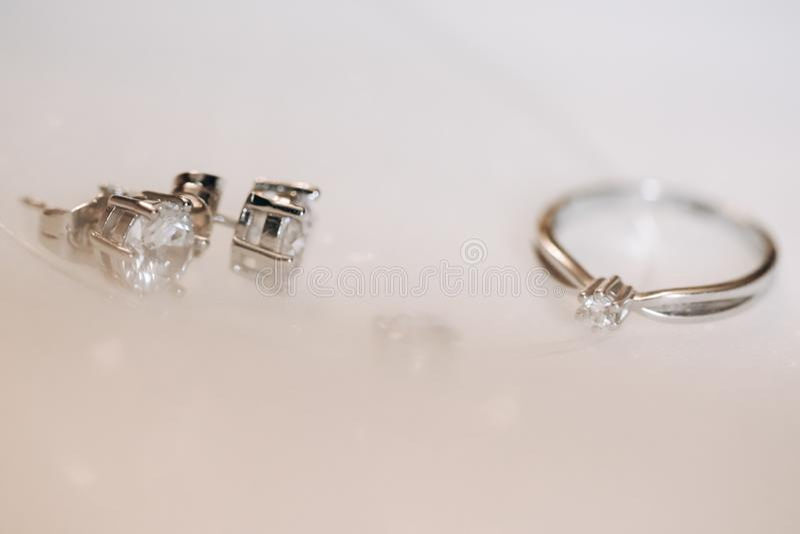 Ring und Ohrringe mit Diamanten auf weißem Hintergrund lizenzfreie stockfotografie