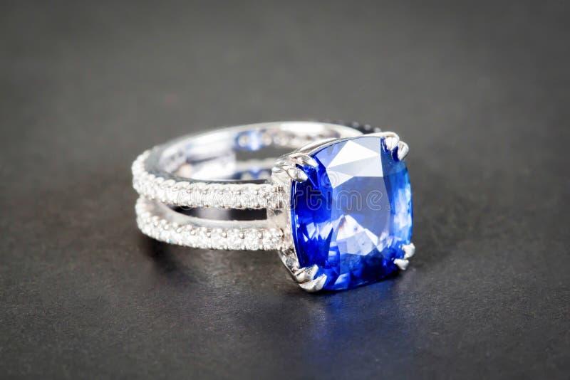 Ring van de juwelier met donkerblauwe saffier op zwarte backgro stock foto
