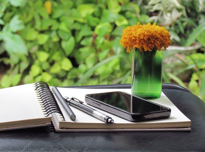 Ringblommablommor i en vasgräsplanflaska på skrivbordet En telefon, pe royaltyfria foton