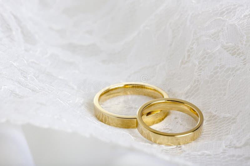 Ringe der goldenen Hochzeit auf weißer Spitze stockfotografie