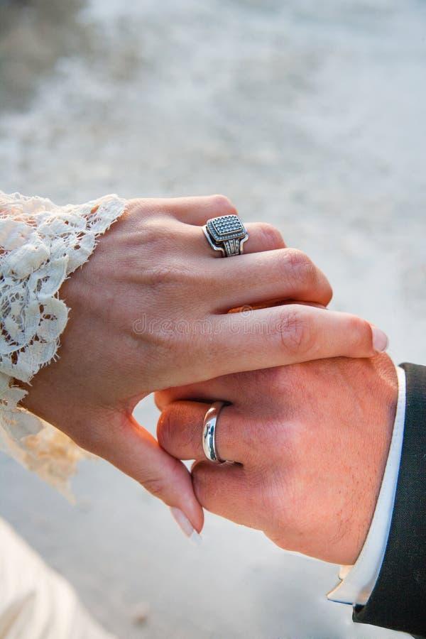 Ringe einer Weinlesebraut und -bräutigams auf der Umfassung von Händen, nachdem an einer Hochzeit geheiratet werden lizenzfreie stockfotografie