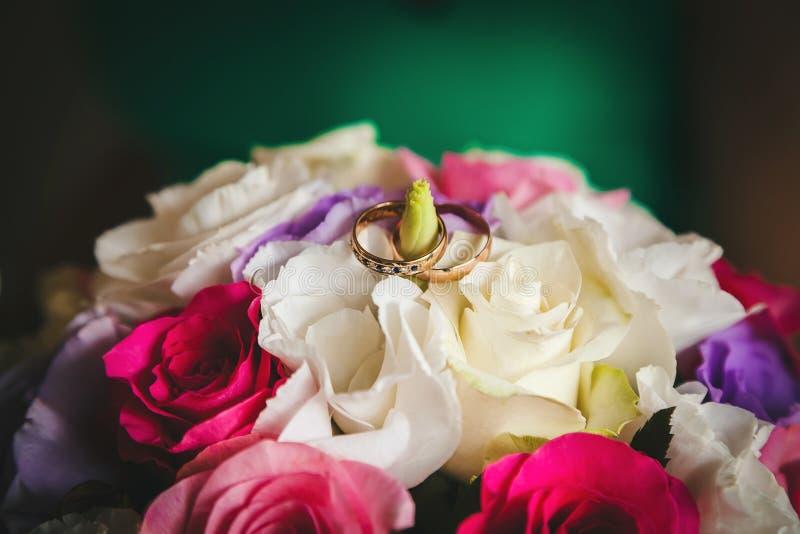 Ringen van de bruid en de bruidegom op het huwelijksboeket van rozen en eustome stock afbeeldingen