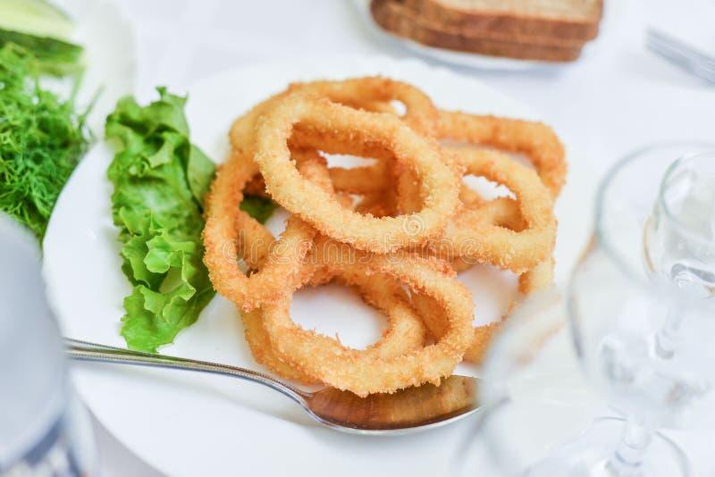 Ringer den djup smet stekte tioarmade bläckfisken calamarien med grön sallad på plattan arkivfoton