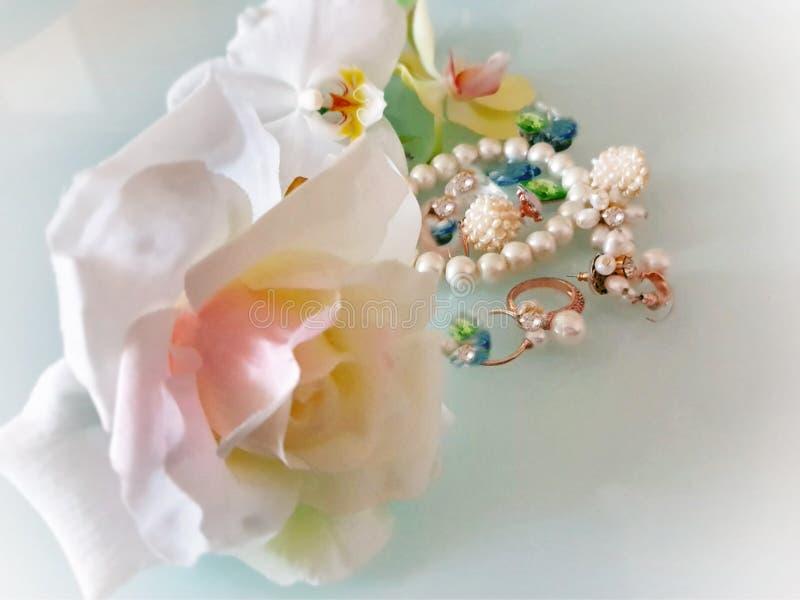 Ringer den vita pärlan för smycken örhängearmbandet med röda rosor för lyxiga smycken för glamourmodedräkten guld-, orkidér på bl fotografering för bildbyråer