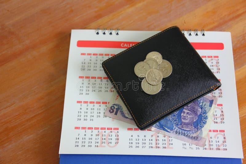 Ringgit e monete della Malesia sul fondo del calendario fotografia stock