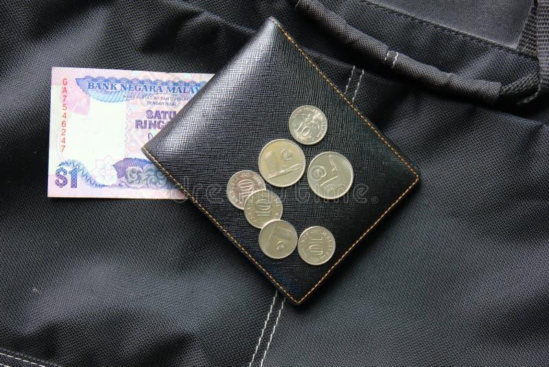 Ringgit e monete della Malesia sul portafoglio nero immagine stock