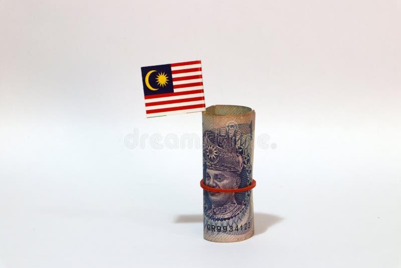 Ringgit rotolato Malesia dei soldi uno della banconota e bastone con la mini bandiera malese su fondo bianco fotografia stock
