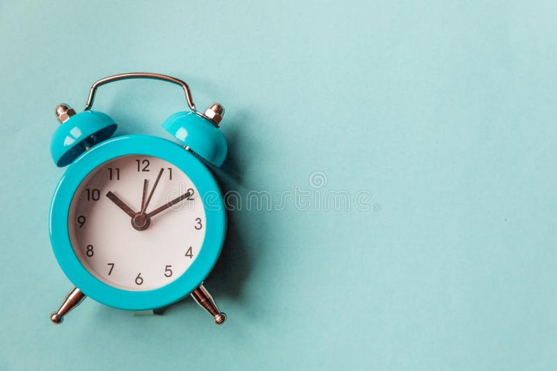 Ringing twin bell vintage classic alarm clock  on blue pastel colorful trendy background. Rest hours time of life good. Morning night wake up awake concept stock photography
