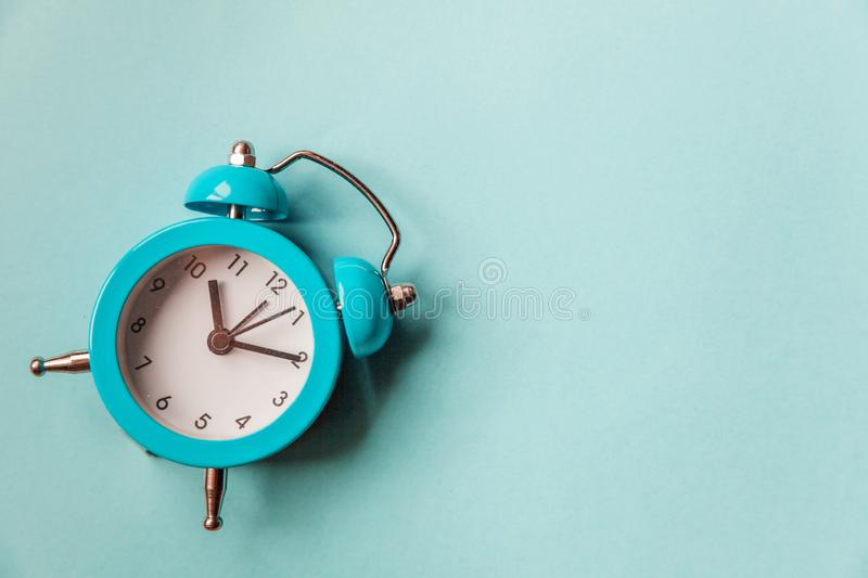 Ringing twin bell vintage classic alarm clock  on blue pastel colorful trendy background. Rest hours time of life good. Morning night wake up awake concept stock photo