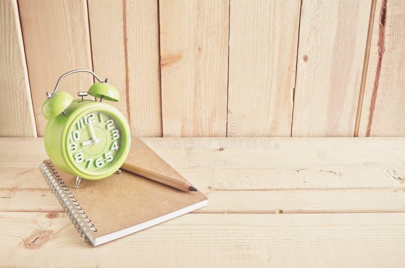 Ringklocka, anteckningsbok och blyertspenna på trätabellen royaltyfria foton