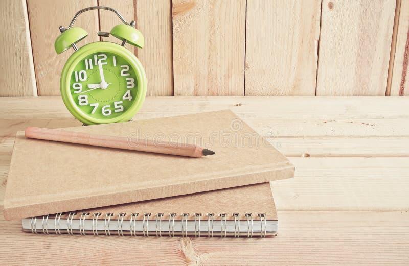 Ringklocka, anteckningsbok och blyertspenna på trätabellen arkivfoto