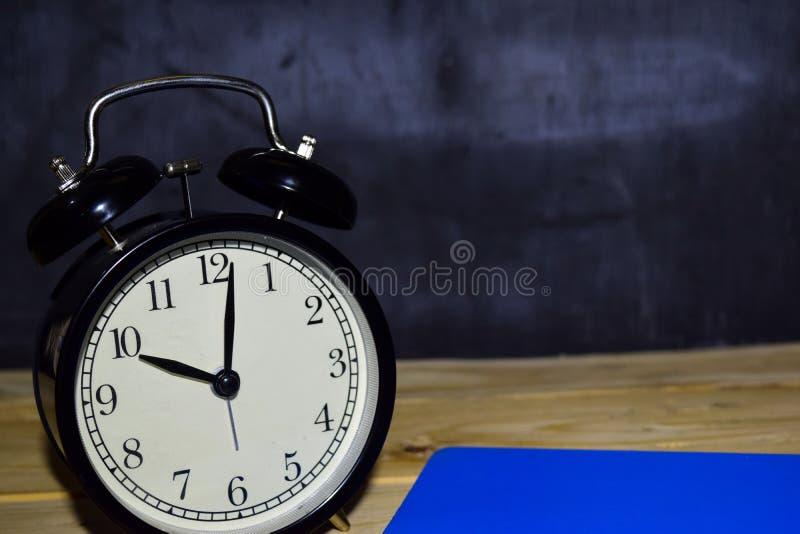 Ringklocka för svart för begreppstappningbakgrund retro på 22 00 e.m. eller 10 00 f.m. och blå bok arkivfoto