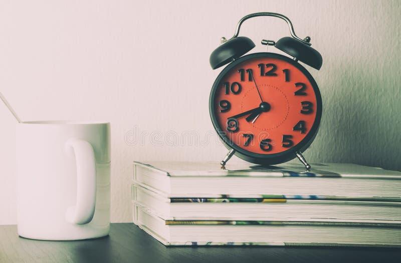 Ringklocka med morgonkaffe och den tomma boken arkivbilder
