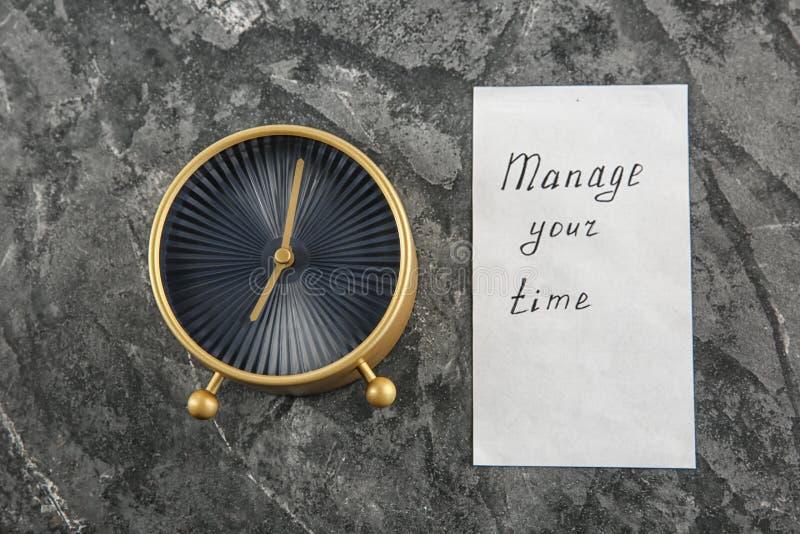 """Ringklocka och ark av papper med uttryck \ """"rätta din tid \"""" på grå texturerad bakgrund royaltyfri foto"""