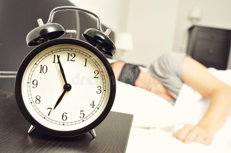 Ringklocka och ung man som sover i säng med en sömnmaskering arkivbilder