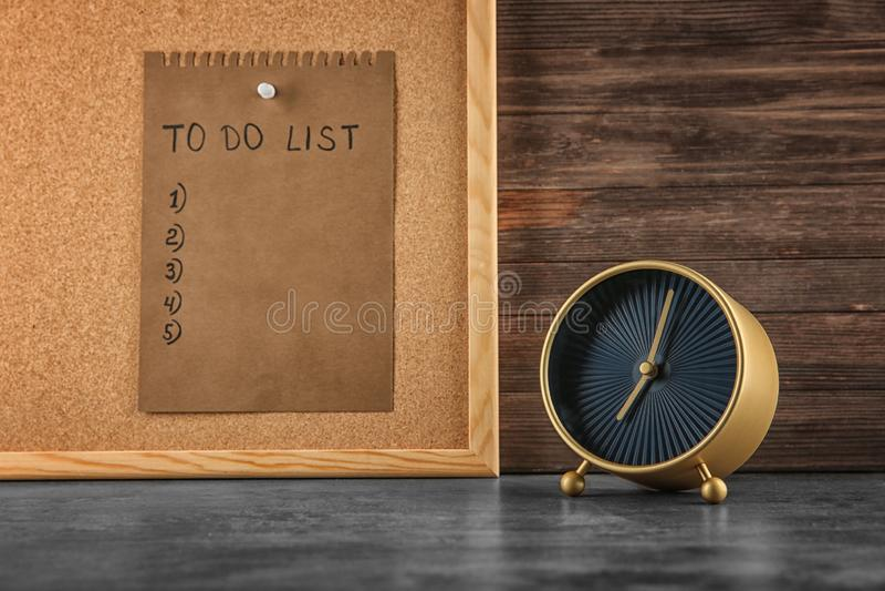 Ringklocka på tabellen och arket av papper med bråklistan ombord Begrepp f?r Tid ledning arkivfoto