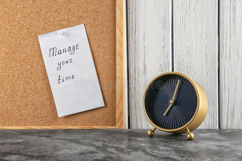 """Ringklocka på tabellen och arket av papper med uttryck \ """"rätta din tid \"""" ombord arkivbilder"""