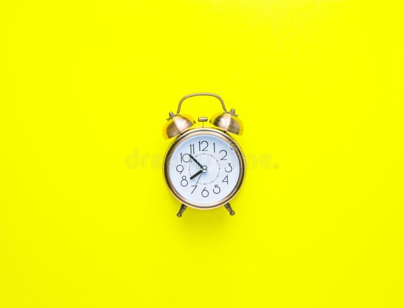 Ringklocka som visar `-klockan för nolla åtta på ljus gul bakgrund Lekmanna- lägenhet Morgonsolljus Ny dagbörjan som upp vaknar e royaltyfria foton