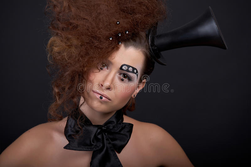 Ringmaster. Beautiful girl with funny make-up - domino, hat, and crystals stock images