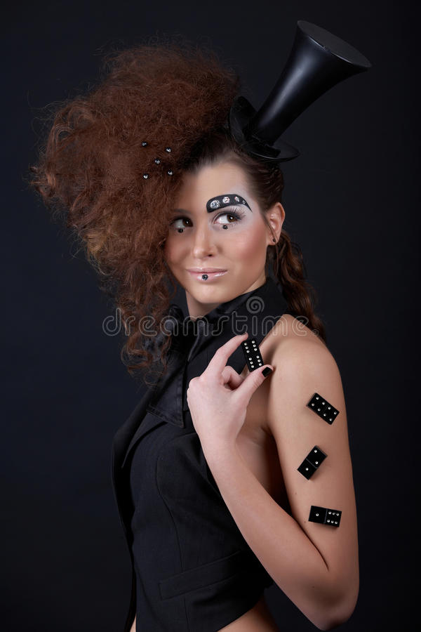 Ringmaster. Beautiful girl with funny make-up - domino, hat, and crystals royalty free stock images