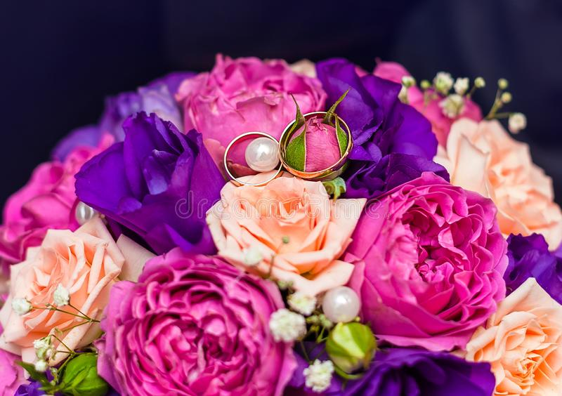 Rings of the bride and groom on the wedding bouquet of roses, eustome and peony roses, close-up. Top view royalty free stock photo