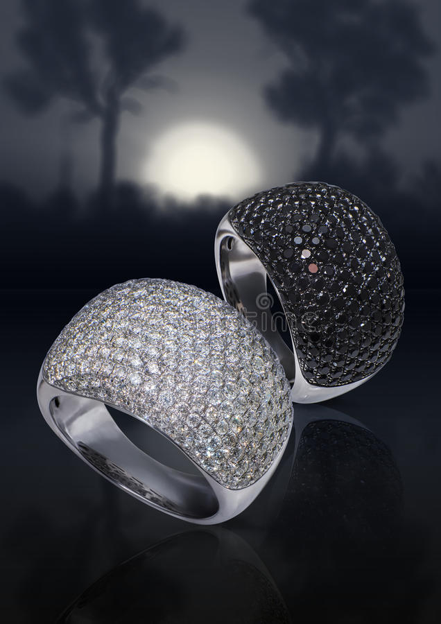 Rings with diamonds. Rings with black and white diamonds on grey background stock photo