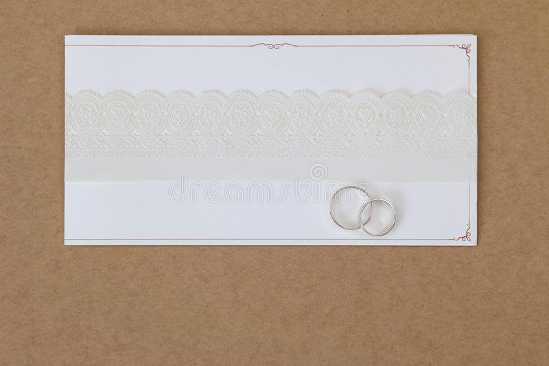 2 rings on a wedding invitation card with white paper lace ribbon. On brown paper background with copyspace royalty free stock image