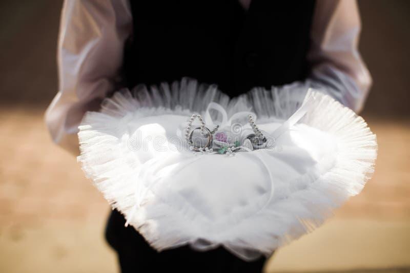 Ringträger des kleinen Jungen, der Nahaufnahme mit zwei die Luxuseheringen hält lizenzfreies stockfoto