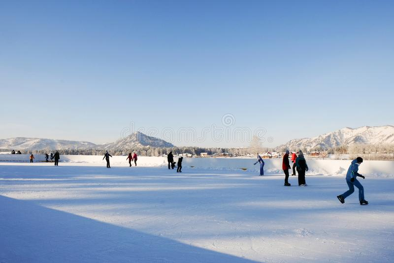 Rink in mountains. Winter holiday scene. Outdoor rink. Mountain lake scenery landscape. Skating outdoor. Winter vacation. Outdoor activity travel, tourism stock photos