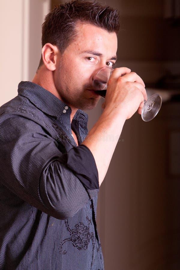 Rinking Wein des jungen stattlichen Mannes stockfoto
