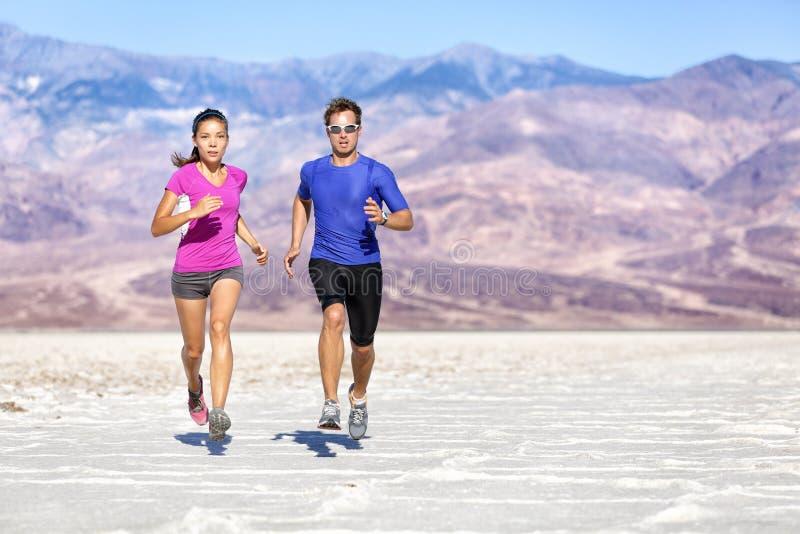 Rinnande beslutsamma par som joggar mot berget royaltyfria foton