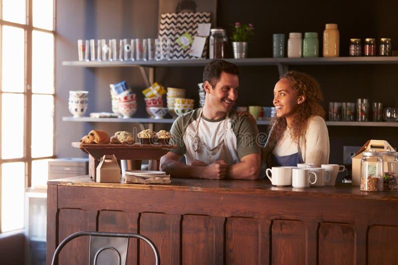 Rinnande coffee shopanseende för par bak räknare arkivfoto