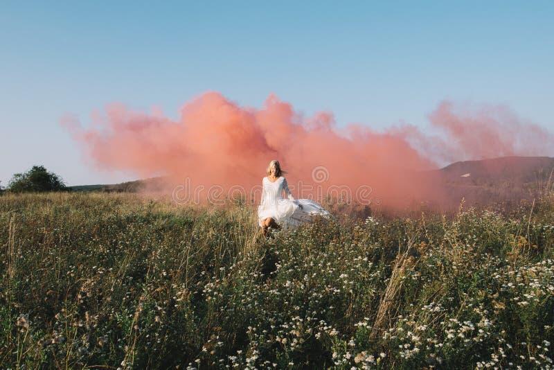 Rinnande det fria för härlig brud med röd rök arkivfoto