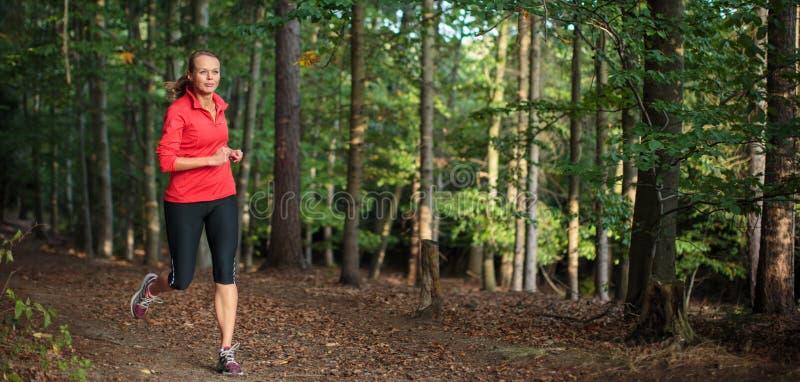 Rinnande det fria för ung kvinna i en skog arkivbilder