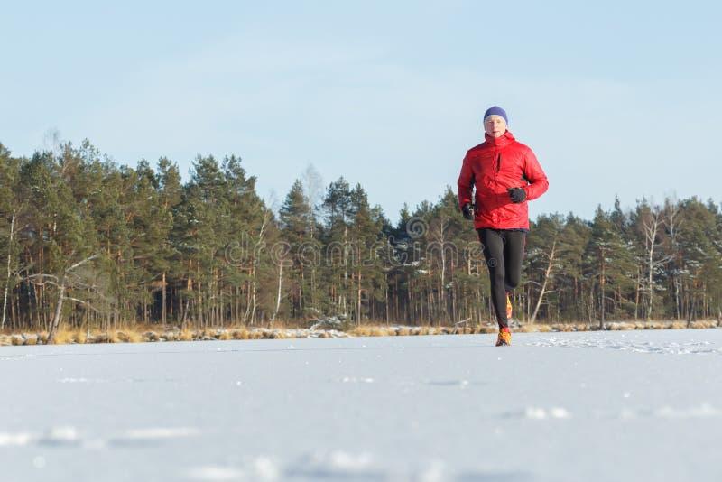Rinnande det fria för ung man i snöig solig skog för vinter royaltyfria bilder