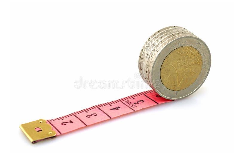 Rinnande euromynt på röd linjal arkivfoto