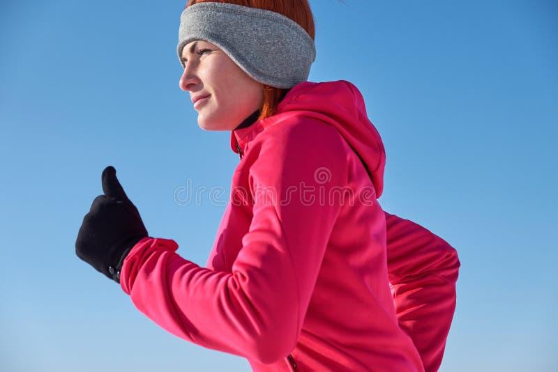 Rinnande idrottsman nenkvinna som sprintar under vinterutbildningsyttersida I royaltyfri fotografi