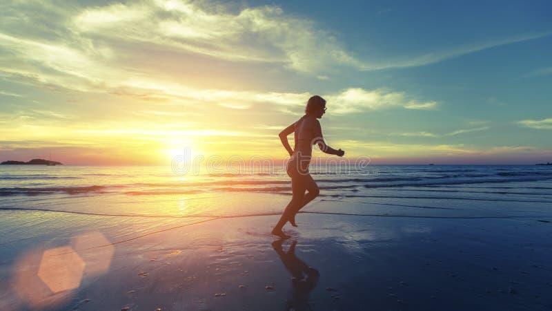 Rinnande kontur av unga flickan på havsstranden under en fantastisk solnedgång arkivbild