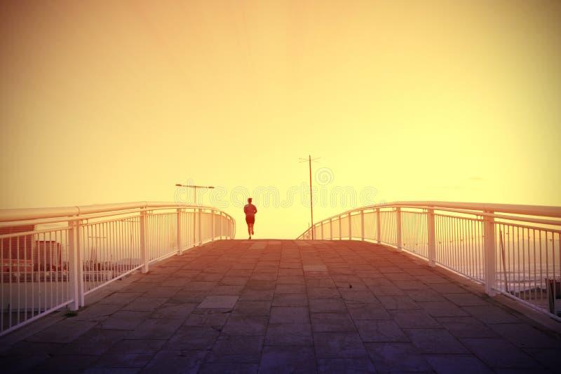 Rinnande korsning för kvinna en bro bredvid beacken på solnedgången tomt kopieringsutrymme royaltyfri fotografi