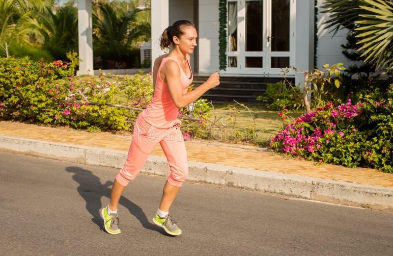 Rinnande kvinna i sommarutbildning Sportkonditionmodell i sportigt royaltyfri foto