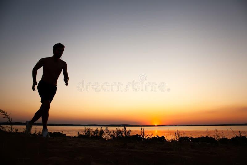 Rinnande mankontur i solnedgångtid Sport- och aktivlivbegrepp arkivfoto