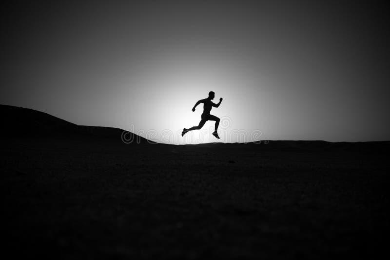 Rinnande mankontur på solnedgånghimmel arkivfoto