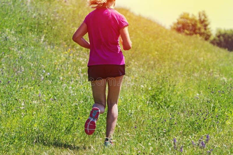 Rinnande maraton för ung kvinna utomhus royaltyfria foton