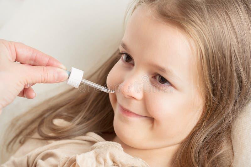 Rinnande näsa i barn Mamman dryper i näsflickadropparna royaltyfria bilder