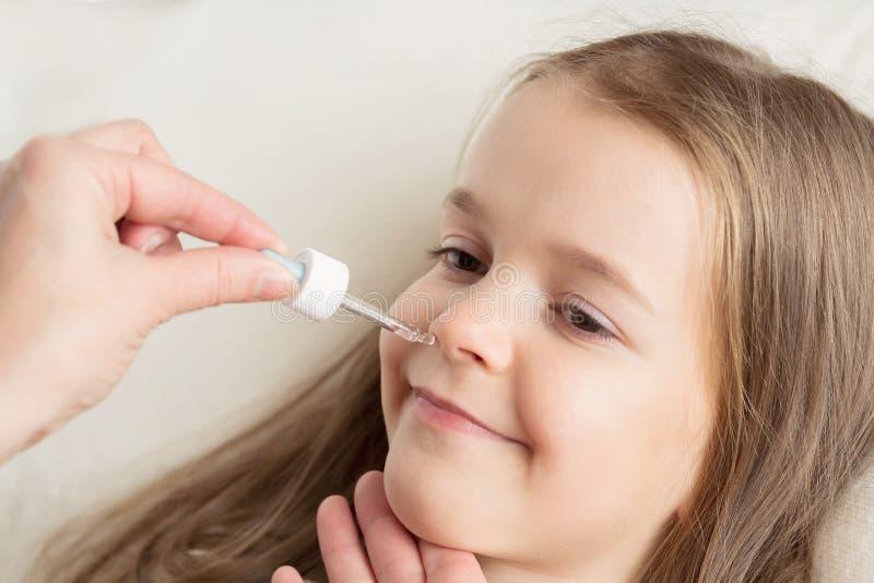 Rinnande näsa i barn Mamman dryper i näsflickadropparna arkivfoto