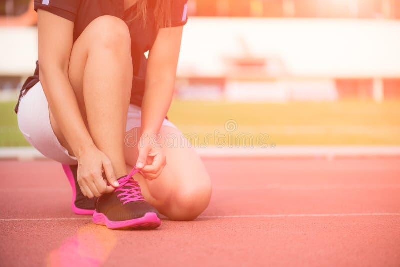 Rinnande skor - closeupen av den unga kvinnan som binder skon, snör åt arkivfoto