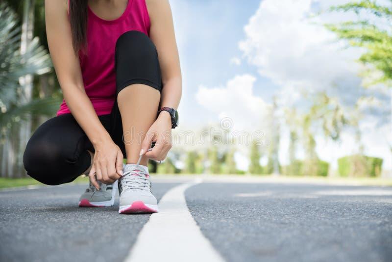 Rinnande skor - closeupen av kvinnan som binder skon, sn?r ?t Kvinnlig sportkonditionl?pare som f?r klar f?r att jogga i tr?dg?rd arkivfoto