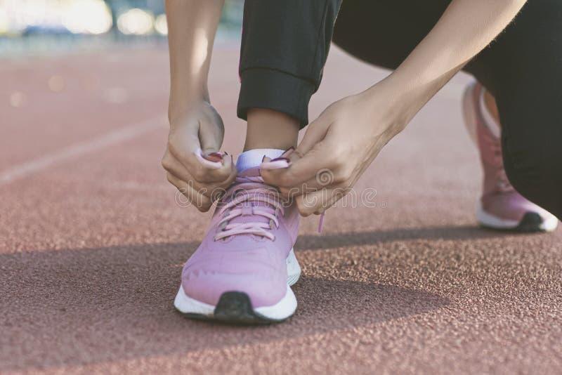 Rinnande skor - closeupen av kvinnan som binder skon, sn?r ?t Kvinnlig sportkonditionl?pare som f?r klar f?r att jogga utomhus fotografering för bildbyråer