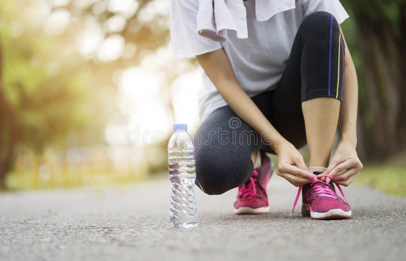 Rinnande skor - kvinnan som binder skon, snör åt Kvinnlig sportkonditionlöpare som får klar för att jogga på trädgården royaltyfri fotografi