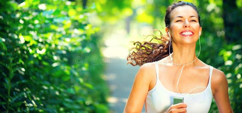Rinnande sportig flicka Ung kvinna för skönhet som joggar i parkera fotografering för bildbyråer